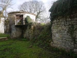 Mur d'enceinte partiellement détruit par la végétation